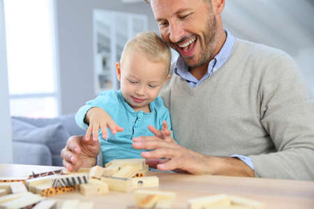 adult toys: Daddy with 2-year-old boy playing with wooden blocks