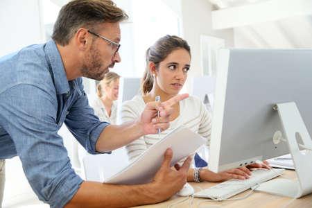 profesor alumno: Profesor con el estudiante que trabaja en la computadora Foto de archivo