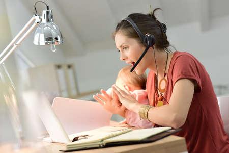 trabjando en casa: Madre joven que consigue ocupado trabajando desde casa con el bebé Foto de archivo