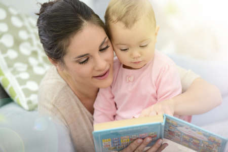 15 months old: Mother and daughter reading book sitting in sofa Stock Photo