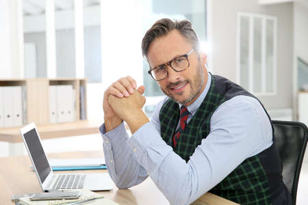 old vintage: Stylish man with eyeglasses sitting in office Stock Photo