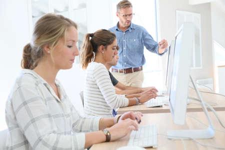 schoolmate: Student girl in class sitting in front of desktop computer