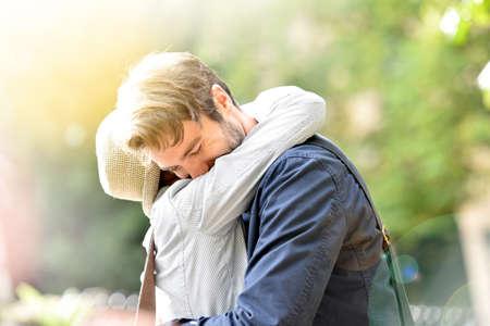 pareja abrazada: Romantic young couple embracing in park, sunlight Foto de archivo