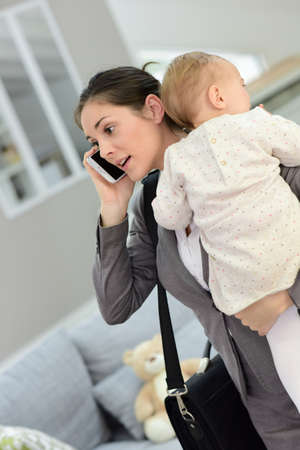 busy person: Busy businesswoman talking on phone and holding baby in arms
