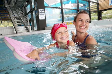 ni�os nadando: Formaci�n Madre e hija en la piscina Foto de archivo