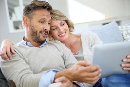 hombres maduros: Pareja de mediana edad que se relaja en el sofá y que usa la tableta