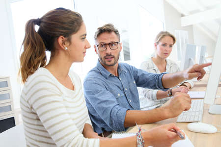 School instructeur helpt studenten met een project werk