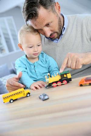 carritos de juguete: Papá con bebé jugando con coches de juguete Foto de archivo
