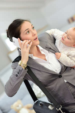 leaving: Busy businesswoman talking on phone and holding baby in arms
