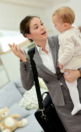 phonecall: Busy businesswoman hurrying in the morning with baby in arms