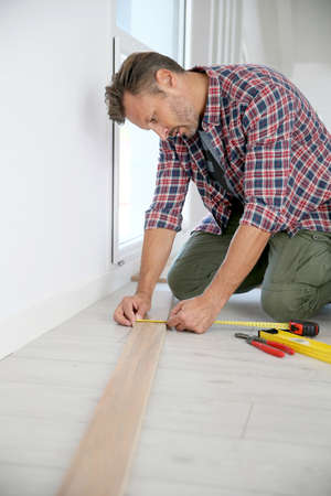 knelt: Cheerful man at home installing new wooden floor
