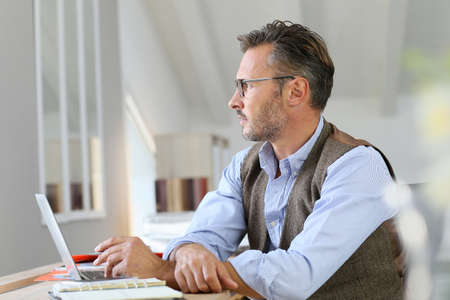 working on computer: Businessman at home looking away through window