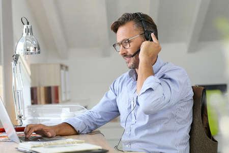 teleworking: Businessman teleworking, headset on Stock Photo