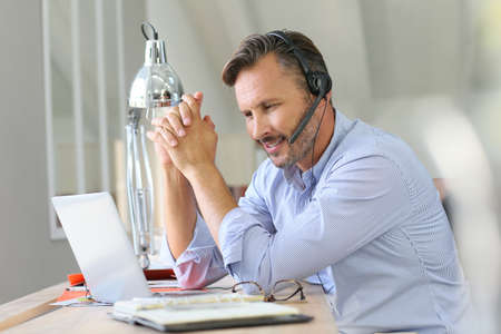 business conference: Businessman teleworking, headset on Stock Photo