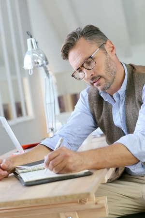 hombre escribiendo: Hombre de negocios de moda con gafas escrito en la agenda Foto de archivo