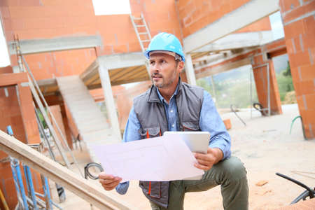 architect: Construction manager checking blueprint on site