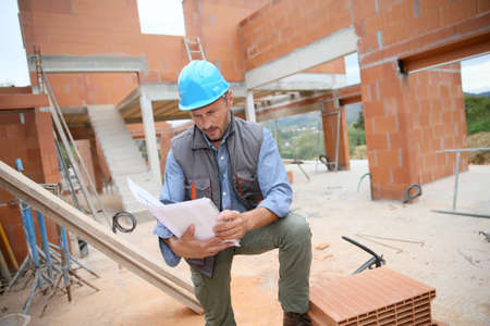 cantieri edili: Construction manager checking blueprint on site