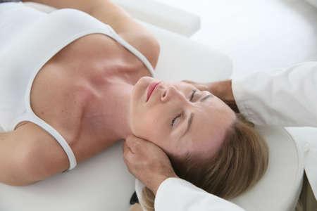 Мануальный терапевт касаясь головой женщины