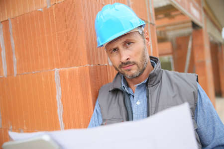 worker man: Construction manager checking blueprint on site