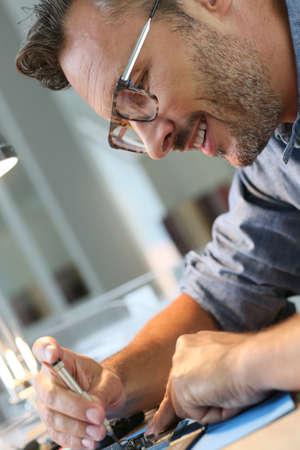 technology career: Man repairing broken smartphone in workshop Stock Photo