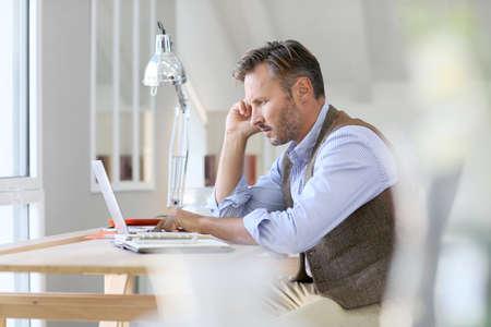 arquitecto: Hombre que trabaja en la computadora port�til Foto de archivo