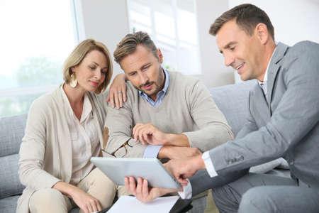 pareja de esposos: Asesor financiero que muestra los términos del contrato en la tableta