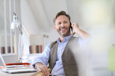businessman phone: Businessman at work talking on the phone