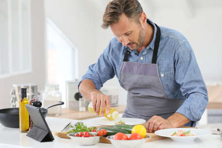 40 years old man: Man in kitchen cooking dish and using digital tablet