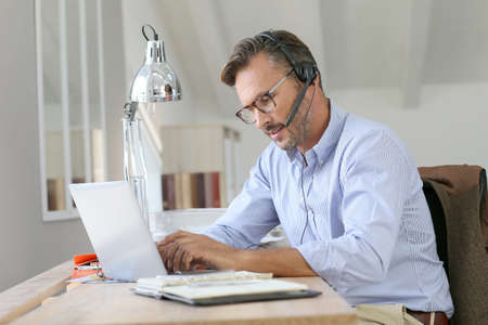 homeoffice: Businessman teleworking, headset on Stock Photo