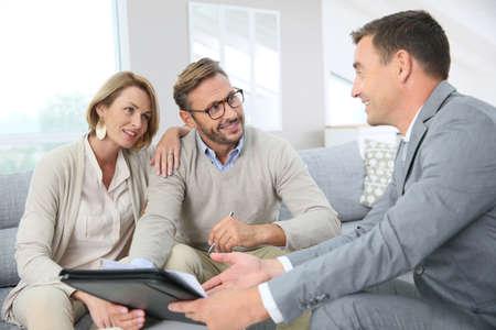 Couple avec contrat de prêt hypothécaire de signature d'agent immobilier