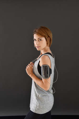 profile view: Profile view of fitness girl with smartphone and earphones, isolated