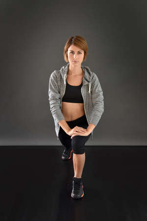 woman black background: Fitness girl stretching legs in gym, isolated Stock Photo