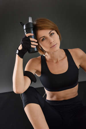 gym floor: Fitness girl sitting on gym floor and holding bottle, isolated