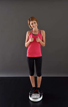 scale weight: Happy fitness girl weighting on scale Stock Photo