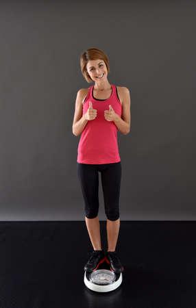 weighting: Happy fitness girl weighting on scale Stock Photo