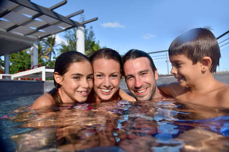 Happy family in swimming-pool, summertime