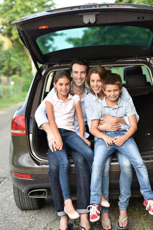 Family sitting in car trunk, ready for vacation Фото со стока