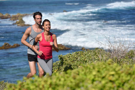 joggers: Couple of joggers running by the sea