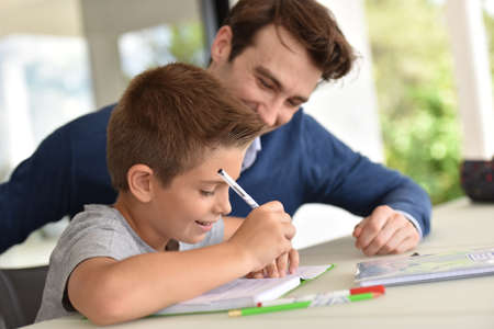 helping: Hombre que ayuda al hijo con la tarea