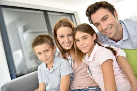family sofa: Portrait of happy family sitting in sofa