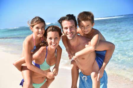 familias felices: Retrato de familia alegre en la playa, llevan a cuestas paseo