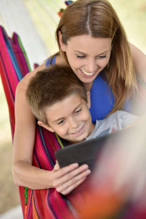 websurfing: Mother and son in hammock using tablet