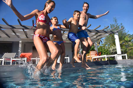 Family jumping into pool swimming-pool Banque d'images