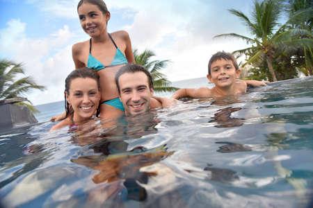 Gezin van vier genieten van zwembad