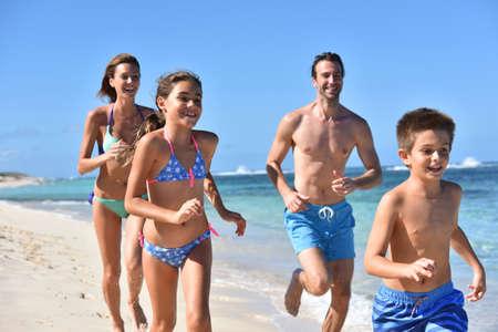 caribbean island: Family runnning on a sandy beach in Caribbean island