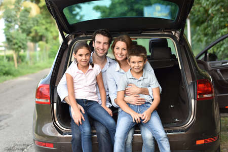 Family sitting in car trunk, ready for vacation Foto de archivo
