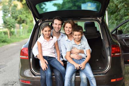 Familie zit in de kofferbak, klaar voor vakantie Stockfoto