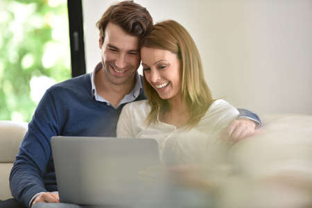 30 years: Couple at home using laptop computer