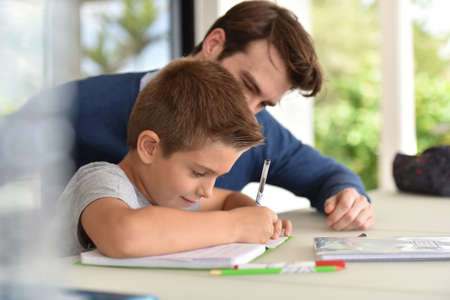 father and child: Man helping son with homework