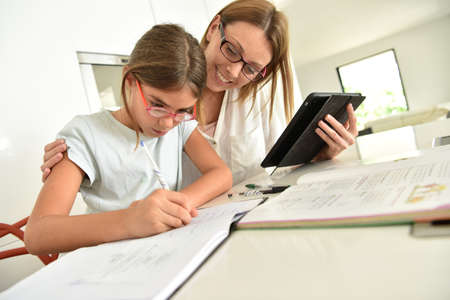 old books: Woman with girl doing homework with tablet